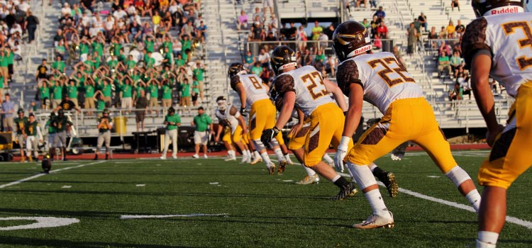 A high school football team with yellow and white jerseys stands on a green field in front of bleachers of cheering fans