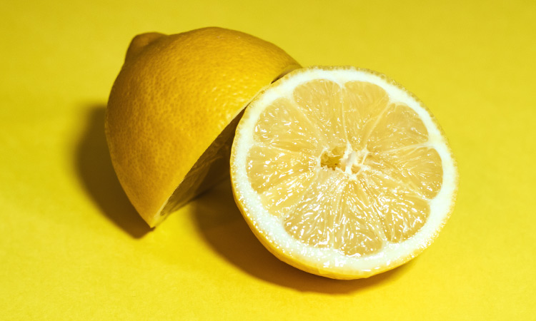 Closeup of a lemon cut in half resting on a yellow counter to be squeezed to brush someone's teeth with lemon juice