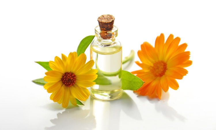 Sunflower oil used for oil-pulling in a small vial with a cork next to a yellow and orange sunflower-like flowers