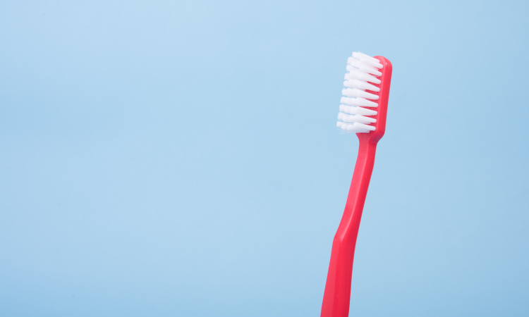 Red old toothbrush with white bristles against a powder blue background
