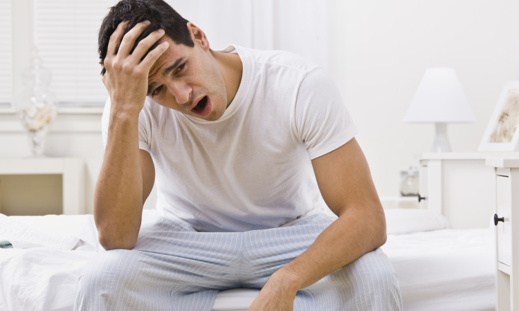 Brunette Man With Obstructive Sleep Apnea Sits On The Edge Of His Bed Yawning In His Pajamas