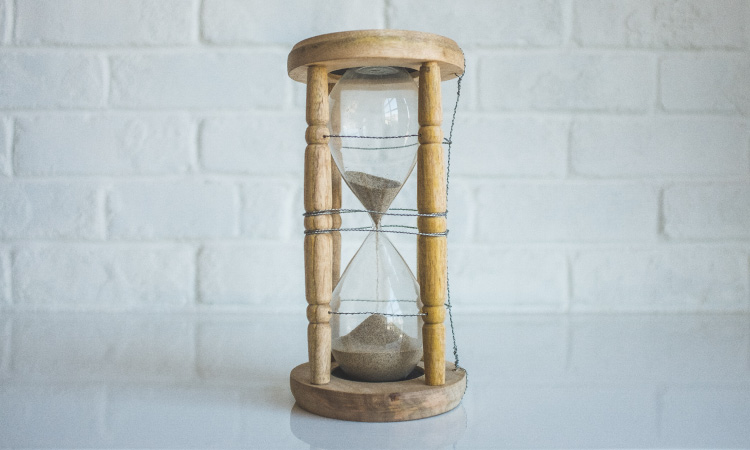 Brown hourglass with sand flowing down to measure time