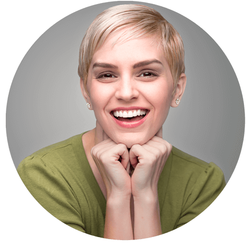 woman with veneers smiling as her chin rests on her hands