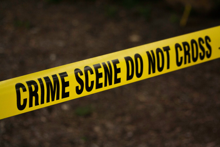 Yellow crime scene tape saying CRIME SCENE DO NOT CROSS that is used in conjunction with forensic dentistry