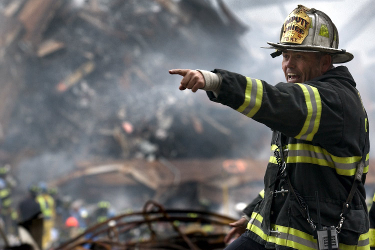 A firefighter in front of a pile of rubble points his finger instructing someone what to do after a fire or earthquake