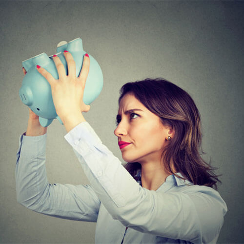 Woman turning a piggy bank upside down