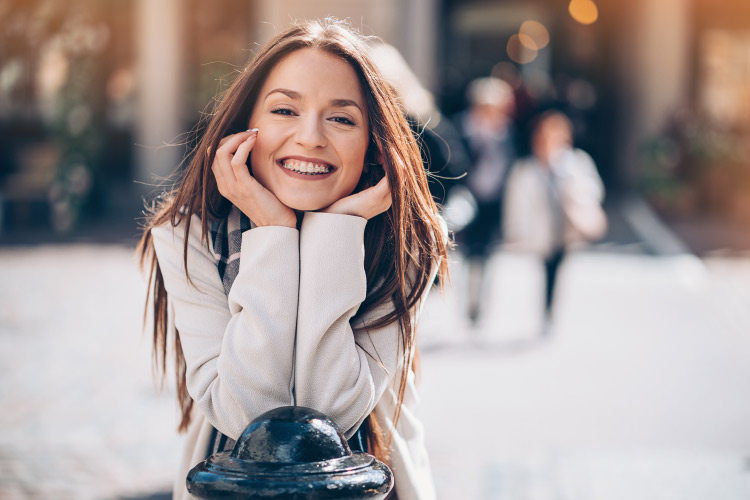 Brunette woman with ceramic braces smiles white in a city square