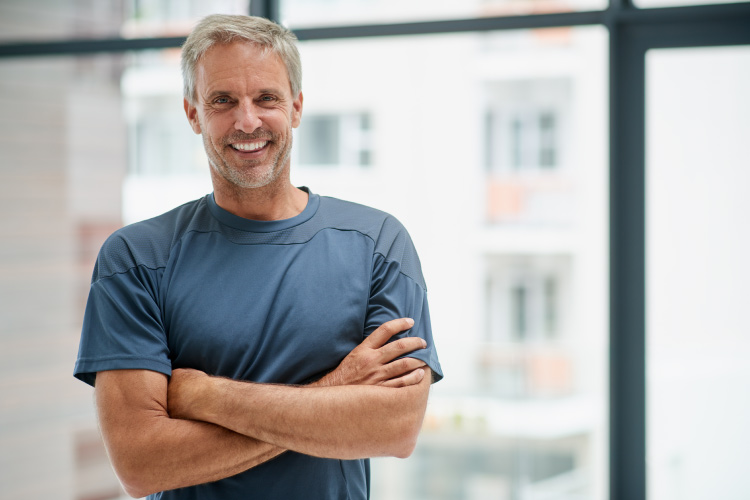 Middle-aged man smiles with dental implants while wearing a gray blue shirt and folding his arms