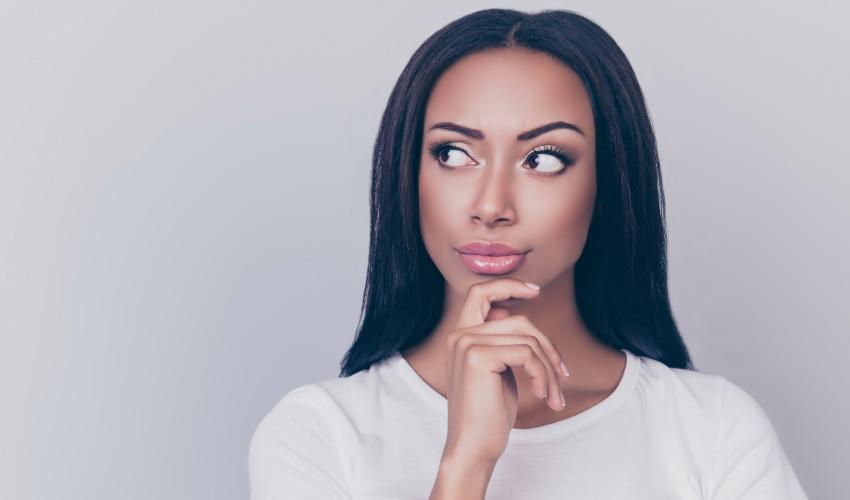 Dark-haired Woman Ponders Her Gum Disease Against A Gray Wall