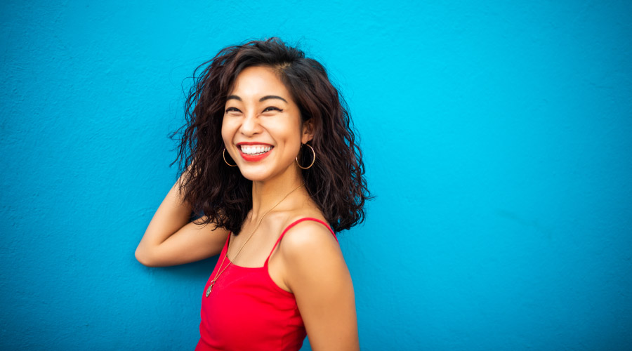 Brunette woman in a red tank top smiles against a blue wall after dental implants