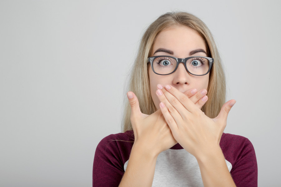 Young Woman Wearing Glasses Covers Her Mouth With Both Hands To Hide Her Sore Gums