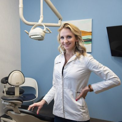 Dr. Harn smiles in a white jacket in a private treatment room at CarolinasDentist in Garner, NC