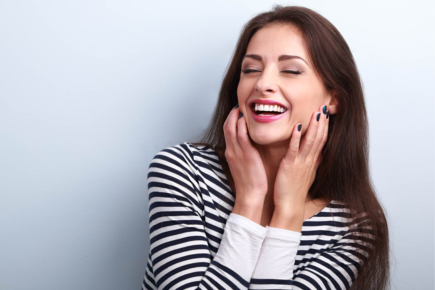 Brunette Woman In A Striped Shirt Smiles With A Bright White Smile After Cosmetic Dentistry